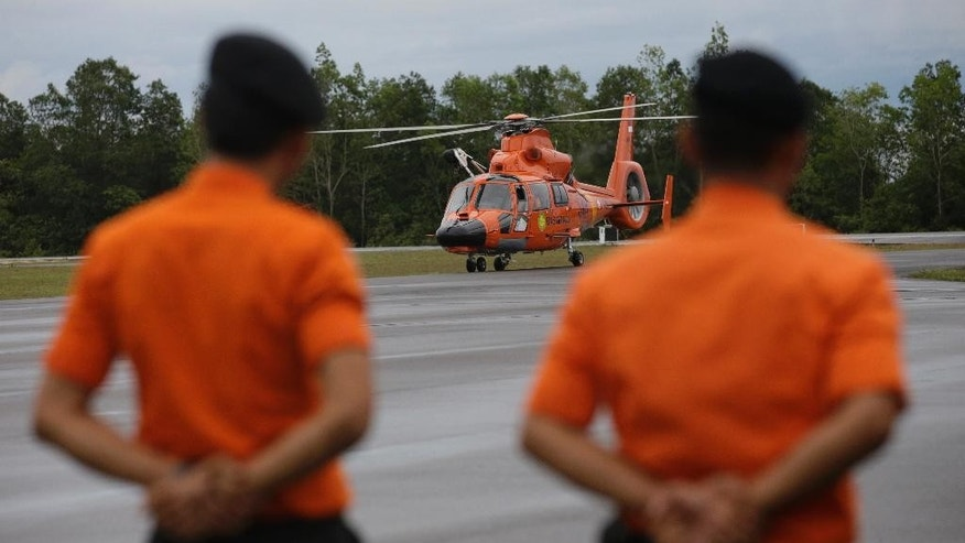 Members of the National Search And Rescue Agency (BASARNAS) watch a helicopter after a search operation of AirAsia Flight 8501 at the airport in Pangkalan Bun, Indonesia, Friday, Jan. 16, 2015. Bad weather and poor underwater visibility have prevented Indonesian navy divers from searching inside the large chuck of AirAsia jet wreckage that's believed to be the fuselage. (AP Photo/Achmad Ibrahim)