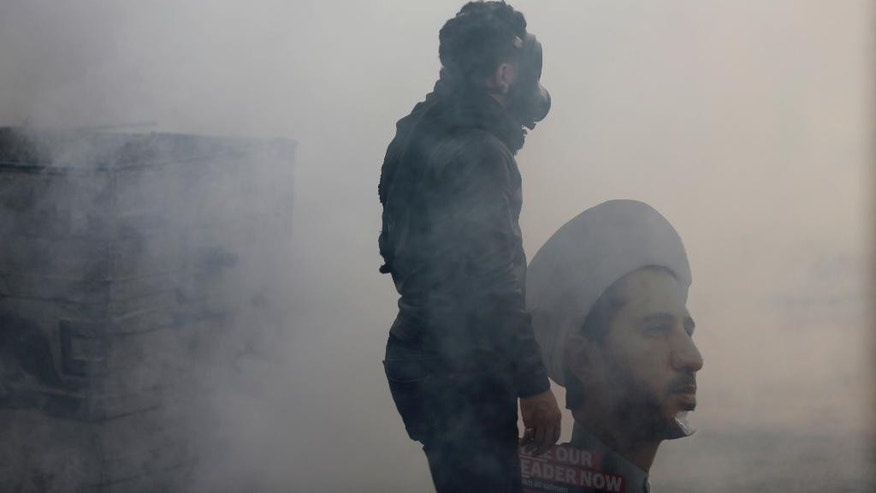 A Bahraini anti-government protester stands with a cutout of jailed Shiite opposition leader Sheikh Ali Salman in tear gas fired by riot police during clashes in Bilad al-Qadeem, Bahrain, Friday, Jan. 16, 2015. Daily clashes have been escalating since Salman's arrest on Dec. 28. (AP Photo/Hasan Jamali)