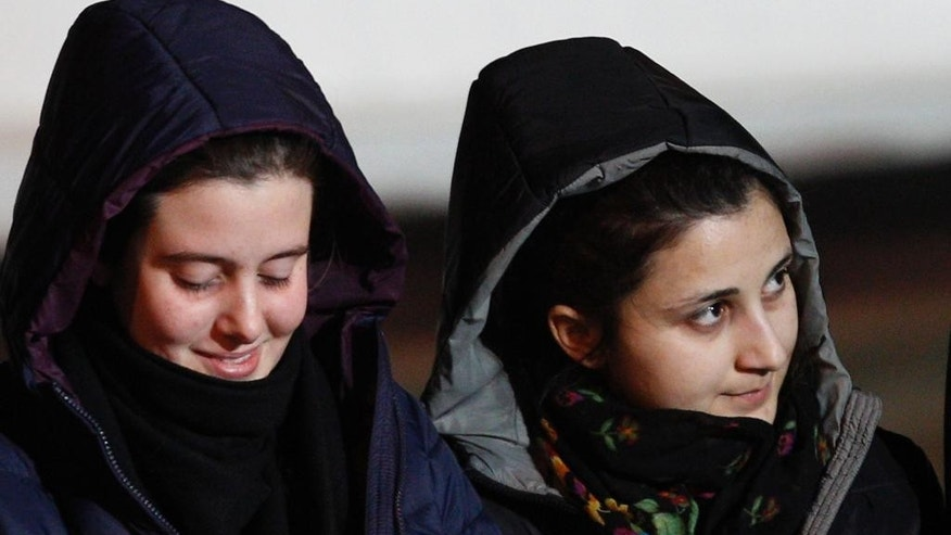 Italian aid workers, 21-year-old Greta Ramelli, left, and 20-year-old Vanessa Marzullo, arrive at Ciampino's military airport, near Rome, early Friday, Jan. 16, 2015. The women, from the northern Lombardy region, disappeared in the northern Syrian province of Aleppo in late July or early August. It wasn't clear at the time who had taken them. They appeared in a video released earlier this month, asking the Italian government to help bring them home, with Ramelli saying they could be killed. Marzullo held a piece of paper with the date Dec. 17, 2014, written on it. (AP Photo/Riccardo De Luca)