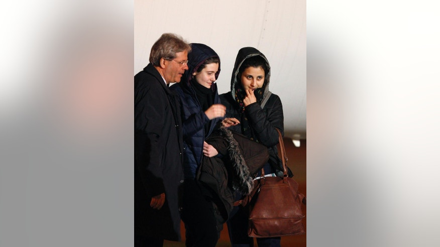 Italian aid workers, 21-year-old Greta Ramelli, center, and 20-year-old Vanessa Marzullo, right, are welcomed by Foreign Minister Paolo Gentiloni as they arrive at Ciampino's military airport, near Rome, early Friday, Jan. 16, 2015. The women, from the northern Lombardy region, disappeared in the northern Syrian province of Aleppo in late July or early August. It wasn't clear at the time who had taken them. They appeared in a video released earlier this month, asking the Italian government to help bring them home, with Ramelli saying they could be killed. Marzullo held a piece of paper with the date Dec. 17, 2014, written on it. (AP Photo/Riccardo De Luca)