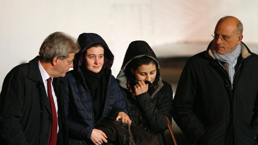 Italian aid workers, 21-year-old Greta Ramelli, second from left, and 20-year-old Vanessa Marzullo, second from right, are welcomed by Foreign Minister Paolo Gentiloni, left, and adviser Claudio Taffuri as they arrive at Ciampino's military airport, near Rome, early Friday, Jan. 16, 2015. The women, from the northern Lombardy region, disappeared in the northern Syrian province of Aleppo in late July or early August. It wasn't clear at the time who had taken them. They appeared in a video released earlier this month, asking the Italian government to help bring them home, with Ramelli saying they could be killed. Marzullo held a piece of paper with the date Dec. 17, 2014, written on it. (AP Photo/Riccardo De Luca)