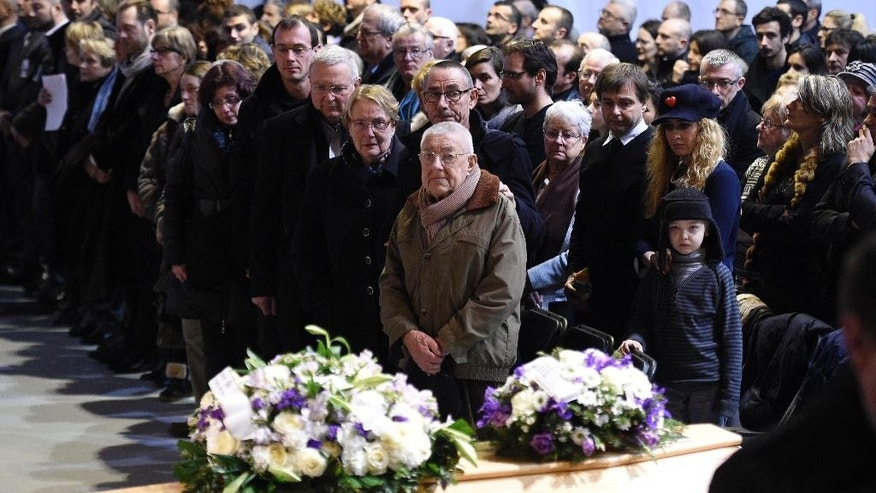 People attend the funeral ceremony of Stephane Charbonnier also known as Charb, the publishing director of Charlie Hebdo, in Pontoise, outside Paris, Friday, Jan. 16, 2015. The country is tense since 20 people, including three gunmen, were killed in last week's rampage. It began at the offices of satirical newspaper Charlie Hebdo, which is burying several staff members Thursday. Charlie Hebdo had been repeatedly threatened for caricatures of the Muslim prophet Muhammad. (AP Photo/Martin Bureau, Pool)