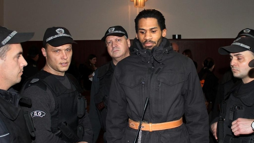 Police officers guard French citizen Fritz-Joly Joachin, 29, center, inside the courtroom before a hearing in the town of Haskovo, Bulgaria Friday, Jan. 16, 2015. A Bulgarian court  considers on Friday a request to extradite a French citizen charged with having been linked to the Kouachi brothers who killed 12 people at the Paris headquarters of Charlie Hebdo magazine last week. (AP Photo)