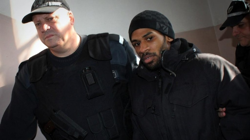 Police officers escort French citizen Fritz-Joly Joachin, 29, right, to the courtroom before a hearing in the town of Haskovo, Bulgaria Friday, Jan. 16, 2015. A Bulgarian court  considers on Friday a request to extradite a French citizen charged with having been linked to the Kouachi brothers who killed 12 people at the Paris headquarters of Charlie Hebdo magazine last week. (AP Photo)