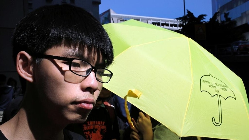 Student leader Joshua Wong arrives at the police headquarters in Hong Kong, Friday, Jan. 16, 2015. Wong, the teenage face of Hong Kong's months long democracy protests last year, struck a defiant note as he turned himself in at police request for possible arrest after authorities vowed to pursue those responsible. (AP Photo/Vincent Yu)