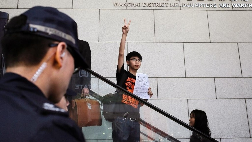 Student leader Joshua Wong flashes a victory sign as he arrives at the police headquarters in Hong Kong, Friday, Jan. 16, 2015.  Wong, the teenage face of Hong Kong's months long democracy protests last year, struck a defiant note as he turned himself in at police request for possible arrest after authorities vowed to pursue those responsible.  (AP Photo/Vincent Yu)