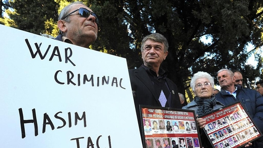 """A protester holding a banner reading """"War criminal - Hashim Thaci"""" during protest against the visit by Kosovo's Foreign Minister Hashim Thaci, in Podgorica, Montenegro, Friday, Jan. 16, 2015. Thaci, the wartime political leader of the Kosovo Liberation Army arrived on a two-day visit in Podgorica where he is to hold several meetings with Montenegrin's top officials. (AP Photo/Risto Bozovic)"""