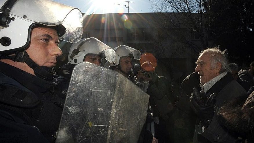 A protester shouts slogans towards a police line during a protest against the visit by Kosovo's Foreign Minister, Hashim Thaci, in Podgorica, Montenegro, Friday, Jan. 16, 2015. Thaci, the wartime political leader of the Kosovo Liberation Army arrived on a two-day visit in Podgorica where he is to hold several meetings with Montenegrin's top officials. (AP Photo/Risto Bozovic)