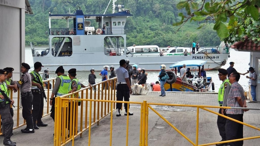 Police officers and security personnel stand guard as a ferry carrying ambulances sets off for Nusakambangan island where the executions of the five of six drug convicts will be performed, at Wijayapura port in Cilacap, Central Java, Indonesia, Saturday, Jan. 17, 2015. Five foreigners and an Indonesian woman sentenced to death on drug charges will be executed by firing squad despite international pleas, Indonesian officials said Saturday. (AP Photo/Wagino)
