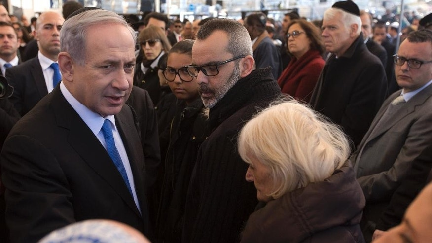 Israeli Prime Minister Benjamin Netanyahu, left, speaks briefly with relatives of Yoav Hattab, one of four French Jews killed in an attack on a kosher grocery store in Paris last week, during their funeral service, in Jerusalem, Tuesday, Jan. 13, 2015. Thousands of mourners joined Israeli leaders and the families of the four Jewish victims of the Paris terror attack for an emotional funeral procession on Tuesday, reflecting the deep sense of connection and concern in Israel over the safety of fellow Jews in Europe. (AP Photo/Jim Hollander, Pool)