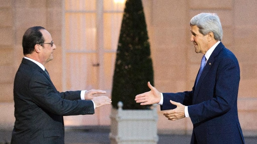 France's President Francois Hollande, left,  welcomes U.S. Secretary of State John Kerry, at the Elysee Palace in Paris,  Friday Jan. 16, 2015. Kerry arrived Friday in the French capital for American solidarity with the French people after last week's deadly terrorist attacks. (AP Photo/Jacques Brinon)