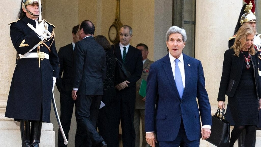 U.S. Secretary of State John Kerry leaves the Elysee Palace in Paris after a meeting with Frend President Francois Hollande, second from left in the background, Friday, Jan. 16, 2015. Kerry arrived in the French capital for American solidarity with the French people after last week's deadly terrorist attacks. At right is U.S. Ambassador in France Jane Hartley. (AP Photo/Jacques Brinon)