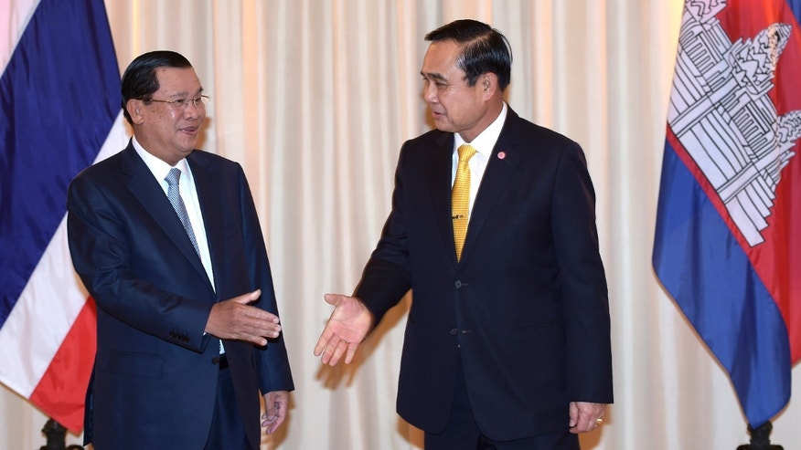 Dec. 19, 2014: Thai Prime Minister Prayut Chan-o-cha, right, shakes hand with Cambodian Prime Minister Hun Sen, left, at Government House in Bangkok.