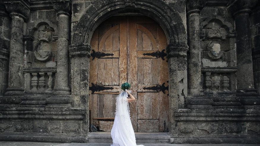 In this Jan. 8, 2015 photo, a Filipino bride arranges her gown before her wedding at a Catholic church in Manila, Philippines. The Philippines is the only country in the world - aside from the Vatican - where divorce is forbidden, a testament to the enduring power of Roman Catholicism that has flourished since Spanish colonizers imposed it nearly 500 years ago. Visiting Pope Francis, the church and many of its followers in this Southeast Asian Catholic stronghold of 100 million believe strongly in the indissolubility of marriage. But a growing number of Catholics would support a change. (AP Photo/Aaron Favila)