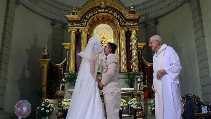 In this Jan. 8, 2015 photo, a Filipino couple kisses after their wedding at a Catholic church in Manila, Philippines. The Philippines is the only country in the world - aside from the Vatican - where divorce is forbidden, a testament to the enduring power of Roman Catholicism that has flourished since Spanish colonizers imposed it nearly 500 years ago. Visiting Pope Francis, the church and many of its followers in this Southeast Asian Catholic stronghold of 100 million believe strongly in the indissolubility of marriage. But a growing number of Catholics would support a change. (AP Photo/Aaron Favila)