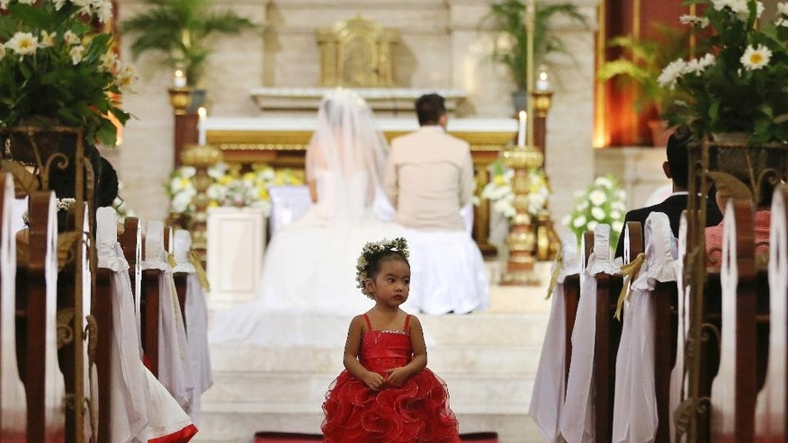 In this Jan. 8, 2015 photo, a Filipino girl joins a wedding ceremony at a Catholic church in Manila, Philippines. The Philippines is the only country in the world - aside from the Vatican - where divorce is forbidden, a testament to the enduring power of Roman Catholicism that has flourished since Spanish colonizers imposed it nearly 500 years ago. Visiting Pope Francis, the church and many of its followers in this Southeast Asian Catholic stronghold of 100 million believe strongly in the indissolubility of marriage. But a growing number of Catholics would support a change. (AP Photo/Aaron Favila)