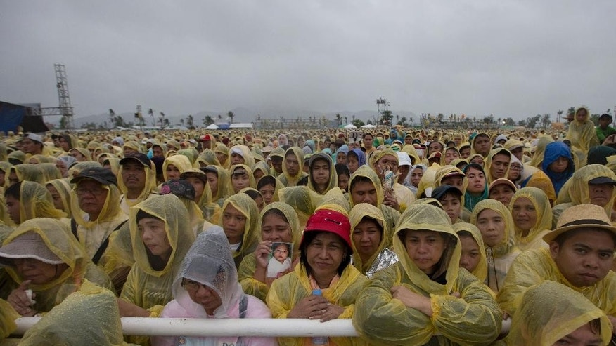 "Wearing a yellow raincoat, Pope Francis gives a thumbs up to the faithful as he arrives in Tacloban, Philippines, Saturday, Jan. 17, 2015. A rain-drenched but lively crowd wearing yellow and white raincoats welcomed Pope Francis in the typhoon-ravage central Philippine city of Tacloban early Saturday, chanting ""Papa Francesco, Viva il Papa!"" (AP Photo/Wally Santana)"