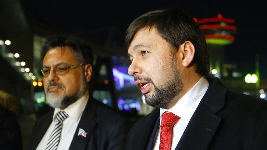 Denis Pushilin, leader of the insurgent Donetsk People's Republic, right, speaks to media at the National airport Minsk, before leaving Belarus, Friday, Jan. 16, 2015. Representatives from Ukraine and Russia, separatist envoys and officials of the Organization for Security and Cooperation in Europe were tentatively set to hold talks Friday in Minsk, Belarus, on ensuring a cease-fire to be monitored by the OSCE. Prospects for Ukraine peace talks remained dim Friday as hostilities intensified between government forces and Russian-backed separatists in the east. (AP Photo/Sergei Grits)