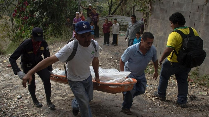 Neighbors and emergency workers carry a body after at least five people were killed, allegedly by gang members, in Ciudad Delgado on the outskirts of San Salvador, El Salvador, Thursday, Jan. 15, 2015. As El Salvador prepares to commemorate the 22nd anniversary of the peace accords that ended the nation's bloody civil war, the nation continues to be gripped by high levels of gang violence. (AP Photo/Salvador Melendez)