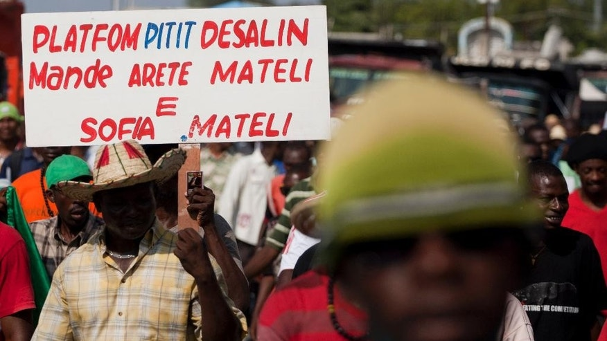 "A protester holds a sign that reads in Creole ""Platfom Pitit Dessaline (a political party) demands the arrest of Martelly and Sofia Martelly,"" as they call for the resignation of President Michel Martelly in Port-au-Prince, Haiti, Friday, Jan. 16, 2015. Friday's protest is the latest in a series of demonstrations demanding Martelly leave office before his term expires next year. (AP Photo/Dieu Nalio Chery)"