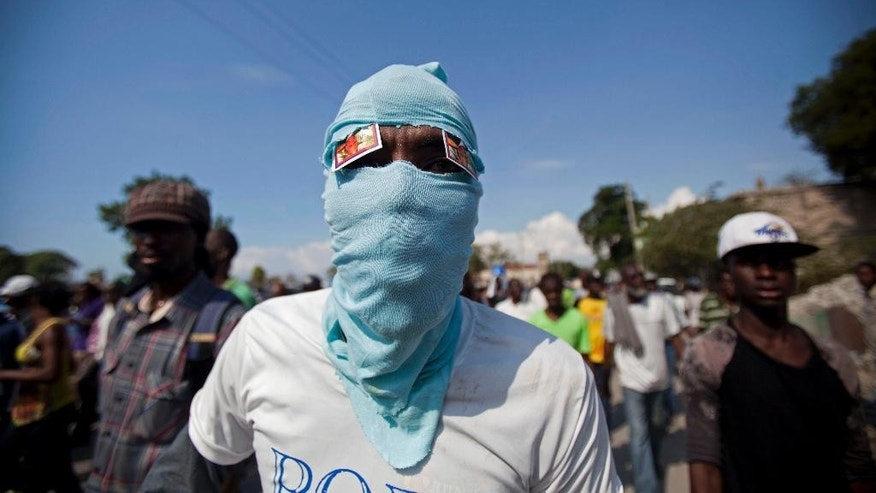 A masked man attends a protest demanding the resignation of President Michel Martelly in Port-au-Prince, Haiti, Friday, Jan. 16, 2015. Friday's protest is the latest in a series of demonstrations demanding Martelly leave office before his term expires next year. (AP Photo/Dieu Nalio Chery)