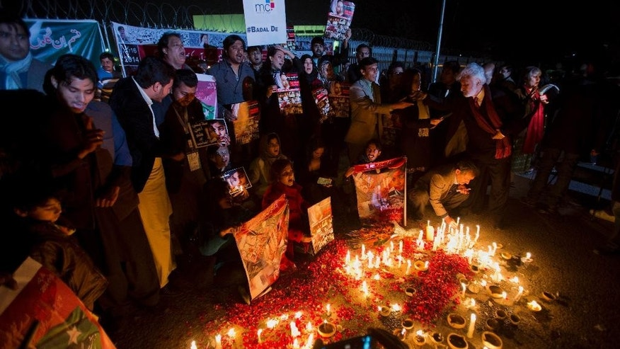 Members of Pakistan's civil society groups light candles and shout anti-Taliban slogans to condemn the militant group's attack on a military-run school in Peshawar, during a rally Friday, Jan. 16, 2015, outside the Parliament building in Islamabad, Pakistan. Civil society groups held protests in Pakistani cities a month after the terrorist attack on Peshawar's Army Public School, where 150 people, mostly children, were killed. (AP Photo/B.K. Bangash)