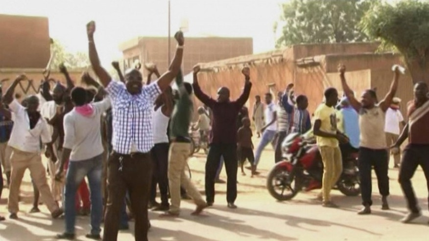 In this video frame grab made available by Associated Press Television News, protesters chant and raise their arms in Niamey, Niger, Saturday Jan. 17, 2015. Security forces in Niger used tear gas Sunday to disperse hundreds of opposition supporters taking part in a banned demonstration in the capital. The political altercation came after 10 people were killed in two days of violent protests against a French publication's cartoon depicting Islam's prophet. (AP Photo/APTN)