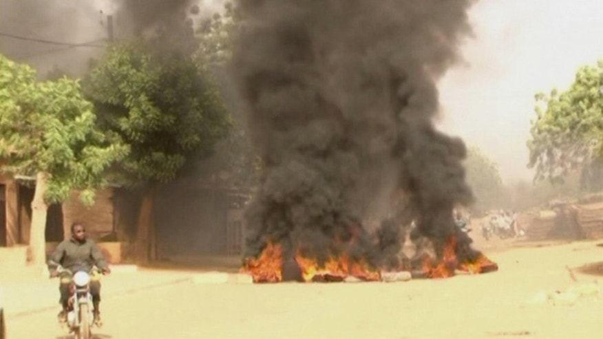 In this video frame grab made available by Associated Press Television News, a motorcyclist rides past a burning roadblock in Niamey, Niger, Saturday Jan. 17, 2015. Security forces in Niger used tear gas Sunday to disperse hundreds of opposition supporters taking part in a banned demonstration in the capital. The political altercation came after 10 people were killed in two days of violent protests against a French publication's cartoon depicting Islam's prophet. (AP Photo/APTN)
