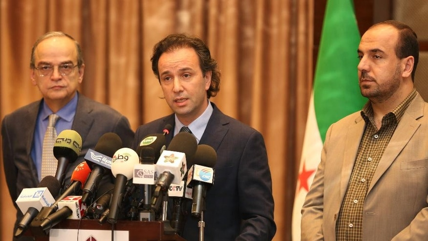 In this picture taken on January 5, 2015, released by the Syrian National Coalition Media Office, Khaled Khoja, the head of the Syrian National Coalition, center, speaks during a press conference, as the former Secretary General Nasr Hariri, right, and the former president Hadi Bahra, left, stand next to him, in Istanbul, Turkey. A Russian initiative to host peace talks this month between the Syrian government and its opponents appears to be unraveling, as prominent Syrian opposition figures shun the planned negotiations over concerns that the framework is flawed and holds little chance of success. (AP Photo/The Syrian National Coalition Media Office)