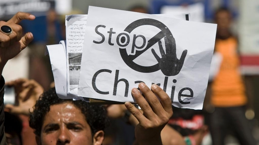 A Yemeni man holds a poster, while chanting slogans during a protest against caricatures published in French magazine Charlie Hebdo in front of the French Embassy in Sanaa, Yemen, Saturday, Jan. 17, 2015. (AP Photo/Hani Mohammed)