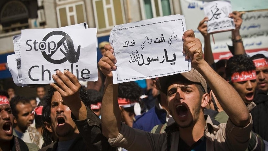 "Yemenis chant slogans during a protest against caricatures published in French magazine Charlie Hebdo in front of the French Embassy in Sanaa, Yemen, Saturday, Jan. 17, 2015. Arabic writing on a poster, center, reads, ""With my father and mother I sacrifice to you, the messenger of Allah,"" meaning the Prophet Muhammad. (AP Photo/Hani Mohammed)"