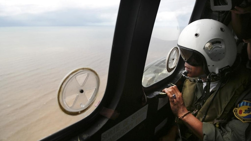 A crew member of an Indonesian Air Force Super Puma helicopter looks out a window  during a search operation for the crashed AirAsia Flight 8501 over the Java Sea, Indonesia, Saturday, Jan. 17. 2015. National Search and Rescue Agency chief Henry Bambang Soelistyo said Friday, that rescue teams discovered more wreckage despite the strong current and poor visibility. (AP Photo/Achmad Ibrahim, Pool)