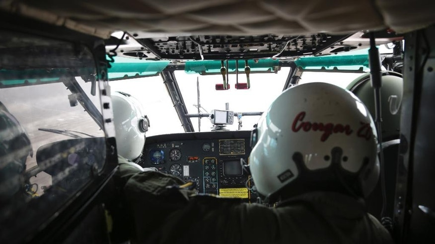 Crew members of an Indonesian Air Force Super Puma helicopter looks out a window during a search operation for the crashed AirAsia Flight 8501 over the Java Sea, Indonesia,Saturday, Jan. 17. 2015. National Search and Rescue Agency chief Henry Bambang Soelistyo said Friday, that rescue teams discovered more wreckage despite the strong current and poor visibility. (AP Photo/Achmad Ibrahim, Pool)