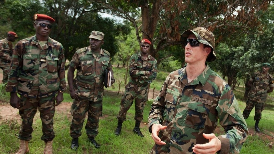 FILE - In this Sunday, April 29, 2012 file photo, U.S. Army special forces Captain Gregory, 29, from Texas, right, who would only give his first name in accordance with special forces security guidelines, speaks with troops from the Central African Republic and Uganda who are searching for Joseph Kony's Lord's Resistance Army (LRA), in Obo, Central African Republic. Dominic Ongwen, a commander of the notorious Ugandan rebel group the LRA, is expected to be flown to the Netherlands Saturday, Jan. 17, 2015 to face international war crimes charges after he surrendered in the town of Obo in a remote corner of the Central African Republic, authorities said. (AP Photo/Ben Curtis, File)