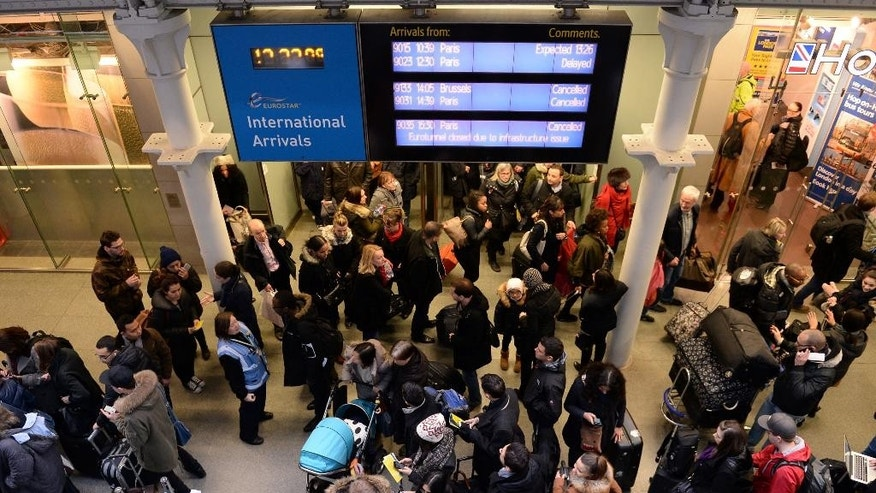 Travellers gather at St Pancras Station, in London, Saturday Jan. 17, 2015. A fire in a truck that was being transported through the Channel Tunnel triggered an alarm which led to suspension of all passenger and freight rail services between Britain and France on Saturday, police said. No injuries were reported. (AP Photo/PA, Stefan Rousseau) UNITED KINGDOM OUT: NO SALES: NO ARCHIVE