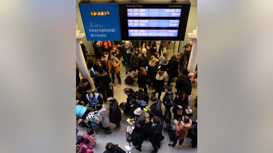Travellers queue at St Pancras Station, in London, Saturday Jan. 17, 2015. A fire in a truck that was being transported through the Channel Tunnel triggered an alarm which led to suspension of all passenger and freight rail services between Britain and France on Saturday, police said. No injuries were reported. (AP Photo/PA, Stefan Rousseau) UNITED KINGDOM OUT: NO SALES: NO ARCHIVE