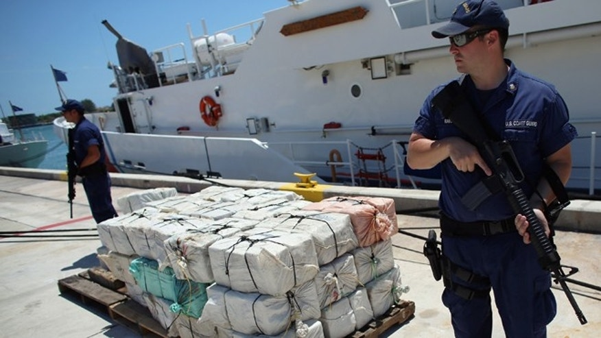 Under heavy security a pile of packages filled with cocaine is piled up after being off loaded from the Coast Guard Cutter Bernard C. Webber after it was seized during Operation Martillo, worth an estimated $27 million on April 26, 2013 in Miami, Florida. (Photo by Joe Raedle/Getty Images)