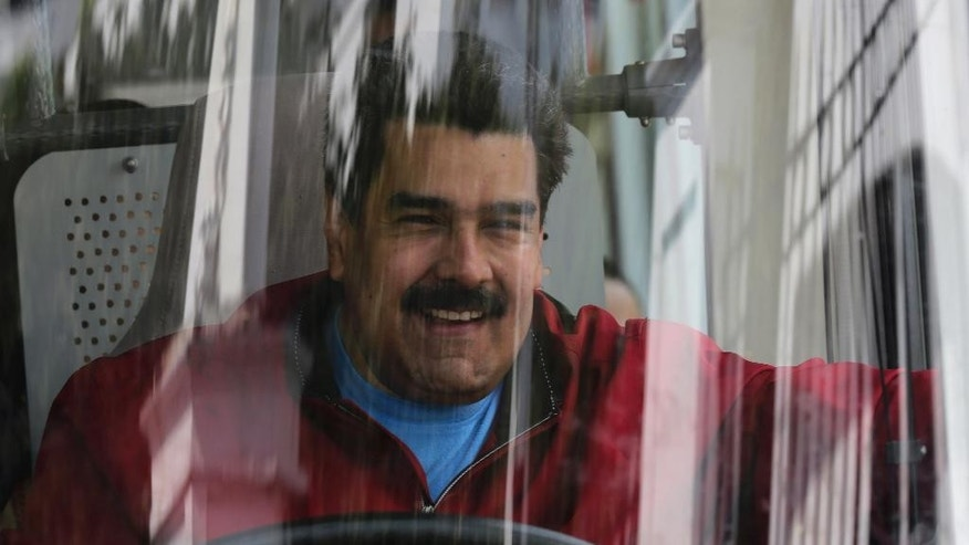 Venezuela's President Nicolas Maduro arrives at the Miraflores Palace, driving a bus from the airport, in Caracas, Venezuela, Saturday, Jan. 17, 2015. Maduro returned home from a two-week fundraising trip Saturday. Mobs of supporters cheered as the socialist South American leader arrived at the presidential palace, driving himself at the head of the motorcade. (AP Photo/Ariana Cubillos)