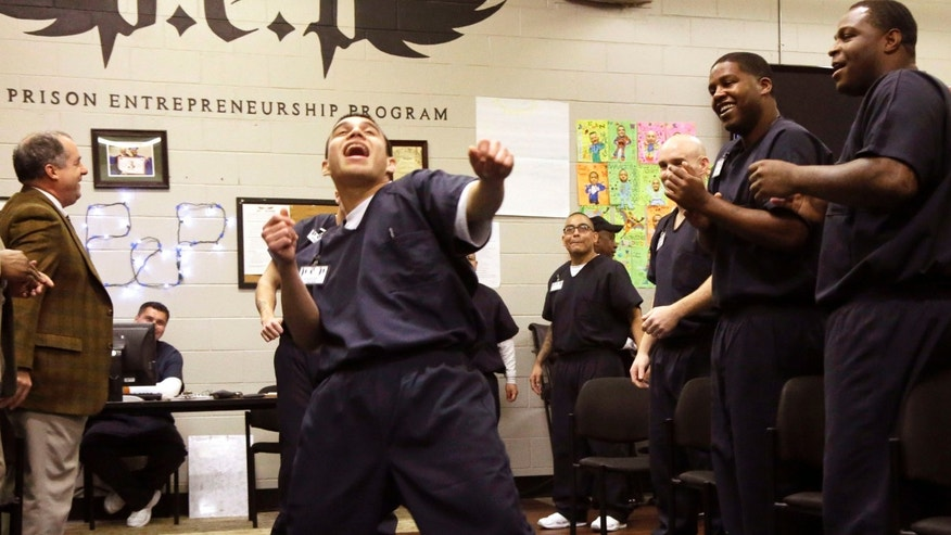 In this photo taken Dec. 12, 2014, prison inmate Nicholas Paz, center, dances down a a line of his classmates in the Prison Entrepreneurship Program, or PEP, right, and program sponsors, in Cleveland, Texas. The rigorous program teaches inmates how to finance a business, how to market their products and how to sell themselves and their stories. PEPâs graduates have a recidivism rate of under 7 percent compared to 23 percent of the overall population in Texas. (AP Photo/Pat Sullivan)