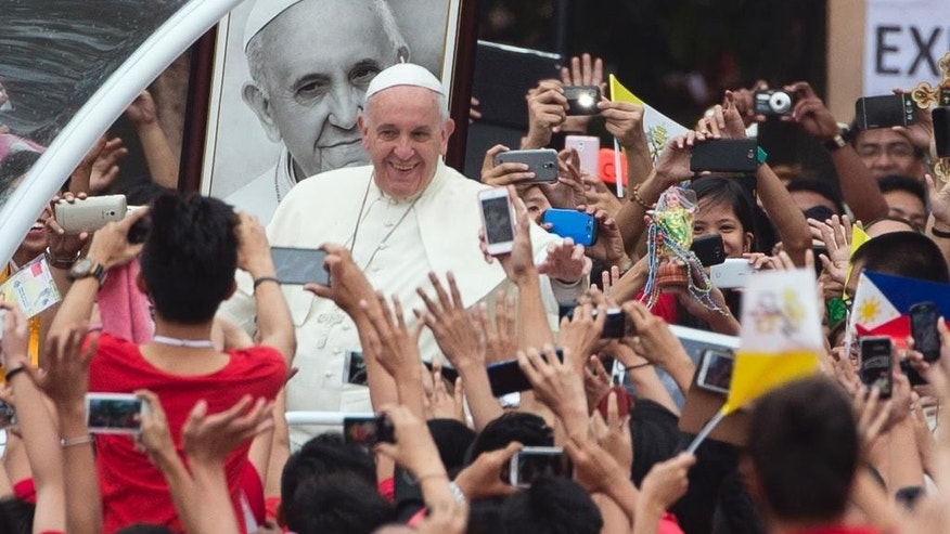 Pope Francis passes past a portrait of himself as he arrives to meet youths in Santo Tomas University in Manila, Philippines, Sunday, Jan. 18, 2015. Francis is in the Philippines on Sunday, the final full day of a weeklong trip that also took him to Sri Lanka.  (AP Photo/Alessandra Tarantino)