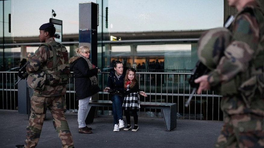 A young girl looks on at French soldiers patrolling at the Roissy Charles de Gaulle airport, in Roissy, north of Paris, Saturday, Jan. 17, 2015. France ordered 10,000 troops into the streets Monday to protect sensitive sites — nearly half of them to guard Jewish schools — as it hunted for accomplices to the Islamic militants who left 17 people dead as they terrorized the nation. (AP Photo/Thibault Camus)