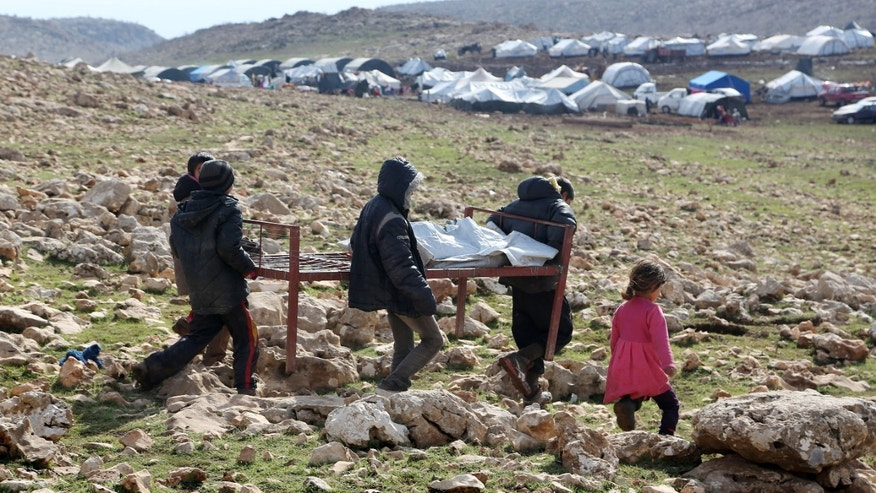 Jan. 12, 2015: Iraqis from the Yazidi minority carry a bed frame on Mount Sinjar in northern Iraq.