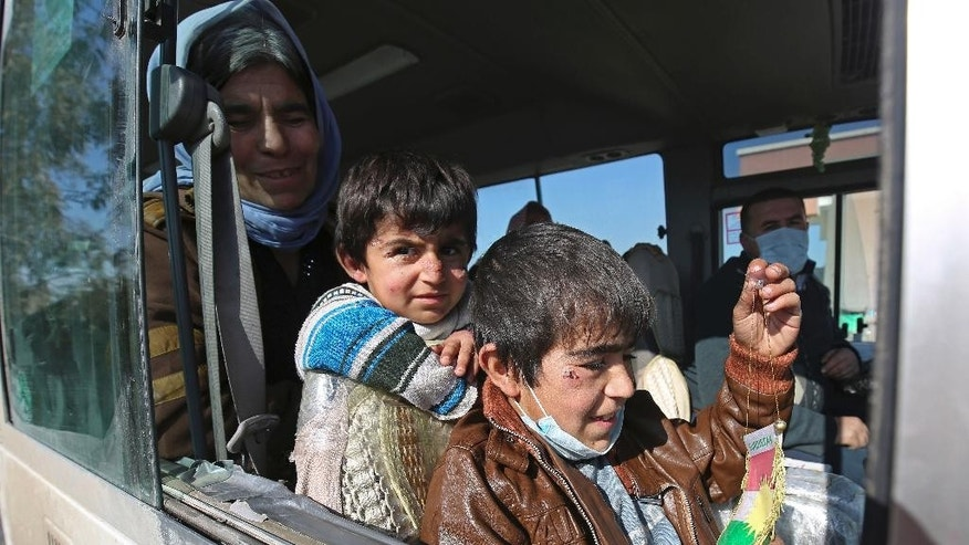 Two Yazidi boys, suffering from several infections from mosquito bites while held by the Islamic State group, wait with their mother inside a bus before being driven to the Kurdish city of Dohuk, in Alton Kupri, outside Kirkuk, Iraq, Sunday Jan. 18. 2015. The Islamic State group released about 200 Yazidis held for five months in Iraq, mostly elderly, infirm captives who likely slowed the extremists down, Kurdish military officials said Sunday. Almost all of the freed prisoners are in poor health and bore signs of abuse and neglect. (AP Photo/Bram Janssen)