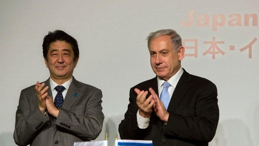 Japan's Prime Minister Shinzo Abe, left, stands with Israeli Prime Minister Benjamin Netanyahu during a conference in Jerusalem, Sunday, Jan. 18, 2015. Abe is on his six-day visit to the Middle East. (AP Photo/Sebastian Scheiner)