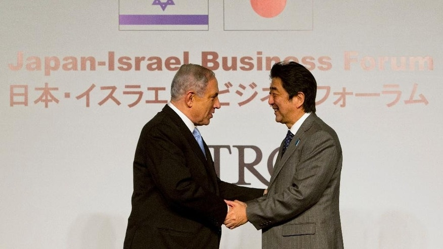 Japan's Prime Minister Shinzo Abe, right, shakes hands with Israeli Prime Minister Benjamin Netanyahu during a conference in Jerusalem, Sunday, Jan. 18, 2015. Abe is on his six-day visit to the Middle East. (AP Photo/Sebastian Scheiner)