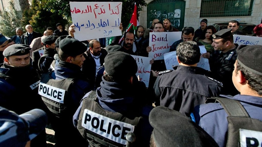 "Palestinian riot police surround protesters, one carrying a banner that reads in Arabic, ""Canada supports terrorism, you are not welcome Baird,"" during Canadian Foreign Minister John Baird's meeting with Palestinian Foreign Minister Riad Malki, in front of the Palestinian foreign ministry in the West Bank city of Ramallah, Sunday, Jan. 18, 2015. Dozens of Palestinian protesters have hurled eggs and shoes at the convoy of the visiting Canadian foreign minister. President Mahmoud Abbas' Fatah party earlier called for a boycott of Baird because of Canada's perceived pro-Israel stance. (AP Photo/Nasser Nasser)"