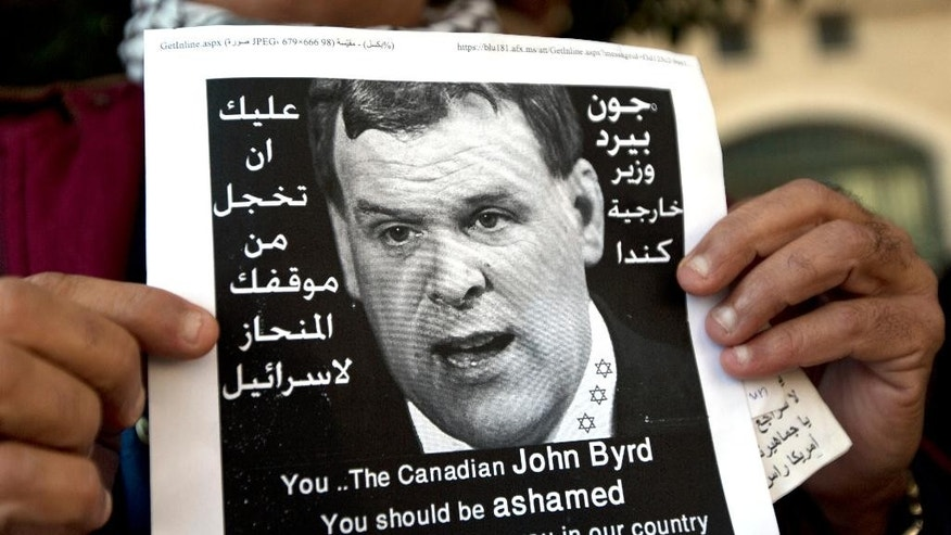 "A Palestinian protester holds a poster with a photo of Canadian Foreign Minister John Baird that reads in Arabic, ""You should be ashamed of your biased position towards Israel,"" during Baird's meeting with Palestinian Foreign Minister Riad Malki, in front of the Palestinian foreign ministry in the West Bank city of Ramallah, Sunday, Jan. 18, 2015. Dozens of Palestinian protesters have hurled eggs and shoes at the convoy of the visiting Canadian foreign minister. President Mahmoud Abbas' Fatah party earlier called for a boycott of Baird because of Canada's perceived pro-Israel stance. (AP Photo/Nasser Nasser)"