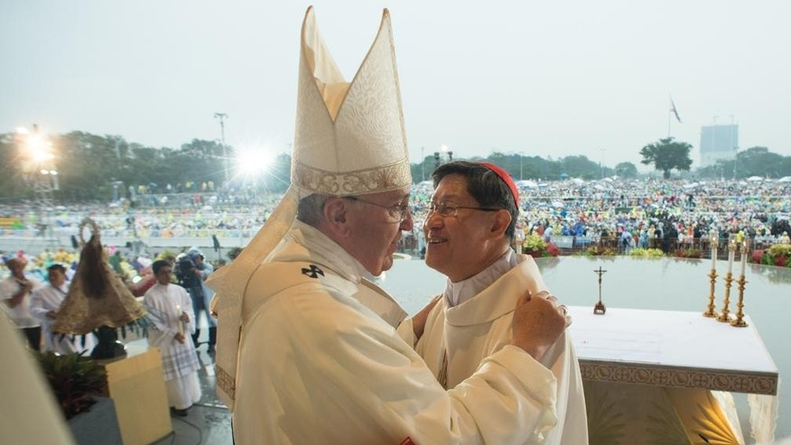 Pope Francis greets Cardinal Luis Antonio Tagle at Rizal Park, in Manila, Philippines, Sunday, Jan. 18, 2015. Millions filled Manila's main park and surrounding areas for Pope Francis' final Mass in the Philippines on Sunday, braving a steady rain to hear the pontiff's message of hope and consolation for the Southeast Asian country's most downtrodden and destitute. (AP Photo/L'Osservatore Romano, Pool)
