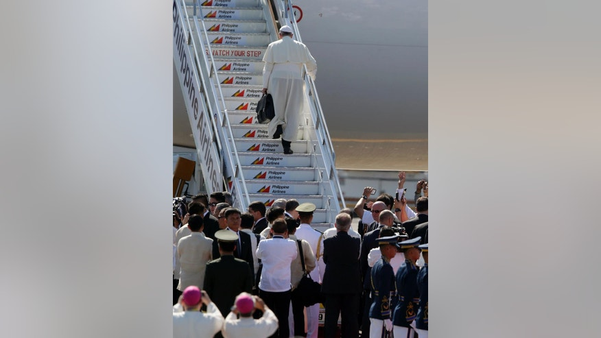 Pope Francis boards his Philippine Airlines chartered plane following a pastoral visit to Manila and typhoon-ravaged Tacloban city Monday, Jan. 19, 2015. Pope Francis flew out of this Catholic bastion in Asia on Monday after a weeklong trip that included a visit to Sri Lanka and drew what Filipino officials says was a record crowd of 6 million faithful in a Manila park where he celebrated Mass. (AP Photo/Bullit Marquez)