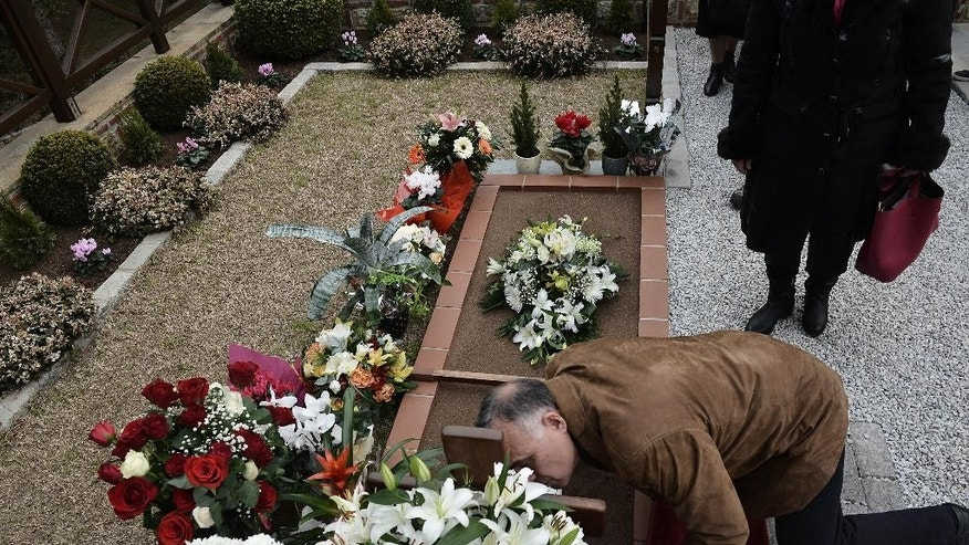 A Christian Orthodox faithful kisses the cross on the grave of St. Paisios in a monastery in the town of Souroti, about 30 kilometers (18 miles) east of Thessaloniki, northern Greece, on Sunday, Jan.18, 2015. Paisios, a monk who spent most of his life in the Mt. Athos monastic community, is the Orthodox Church's newest saint, was canonized last Tuesday, in an unusually short time (20 years, 6 months) after his death, in part due to his popularity among the faithful, who considered him a wise man and a prophet. (AP Photo/Giannis Papanikos)
